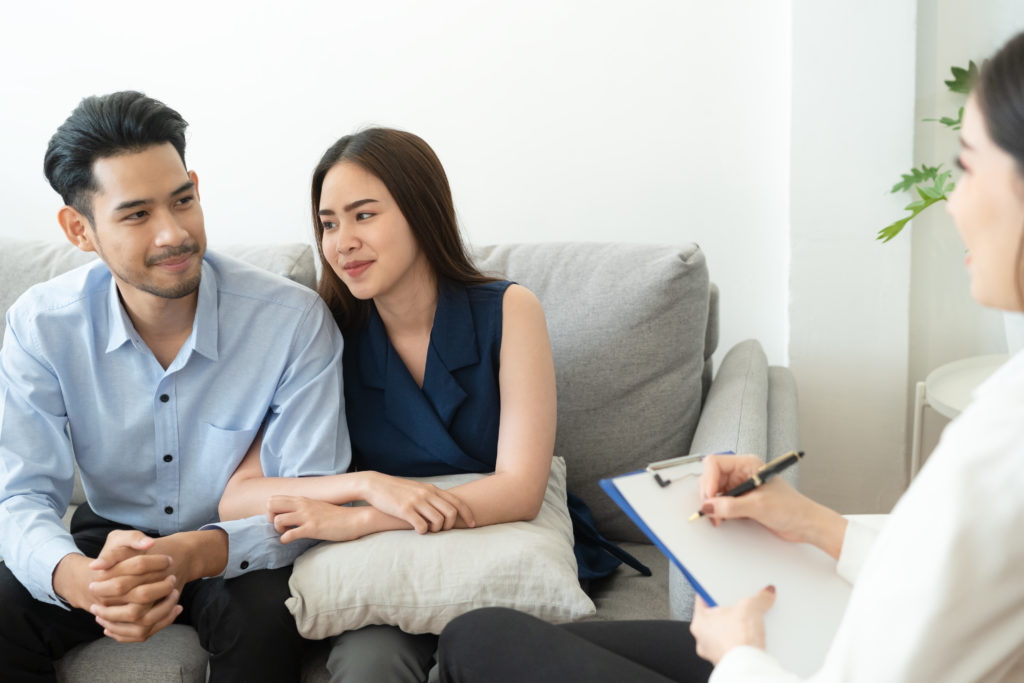 Asian couple sitting on the couch in the room to consult mental health problems by doctor, Health and illness concepts